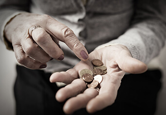 Older person counting coins in her palm