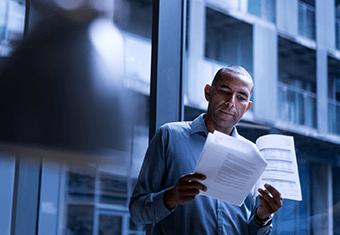 man inspects paperwork